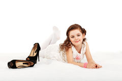 Portrait of a pretty little fun fashion girl lying on a fluffy r Royalty Free Stock Images