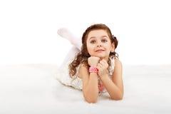 Portrait of a pretty little fun fashion girl lying on a fluffy r Stock Image