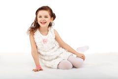 Portrait of a pretty little fun fashion girl sitting on a fluffy Royalty Free Stock Photos