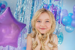 Portrait of Pretty little girl with a big eyes on a balloons background. Portrait of Pretty little girl with a big eyes on a color balloons background Royalty Free Stock Photo