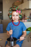 Portrait of a pretty little girl in blue dress and with curlers on a kitchen Stock Image