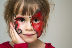 Portrait of pretty little girl with butterfly painting on her fa. Ce stock photography