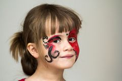 Portrait of pretty little girl with butterfly painting on her fa. Ce royalty free stock photos