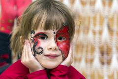 Portrait of pretty little girl with butterfly painting on her fa. Ce stock photos