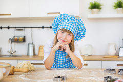 Portrait of pretty little girl in a cook clothes looks on a kitchen. A dough is near Stock Images