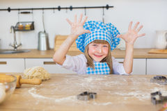 Portrait of pretty little girl in a cook clothes looks shows her fingers on a kitchen Royalty Free Stock Photos