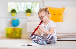 Portrait of pretty little girl with flute on floor Stock Photography