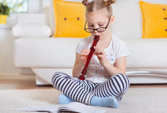 Portrait of pretty little girl with flute on floor Royalty Free Stock Photo