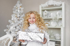 Portrait of Pretty little girl holds a gift box at hands and smiles in a light new year decoration studio Royalty Free Stock Photo