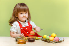 Pretty little girl paints eggs Royalty Free Stock Photography