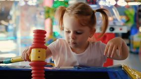 Portrait of a pretty little girl with ponytails playing with a gaming machine. In the arcade. Concept of holiday for children and entertainment complexes. Full stock video
