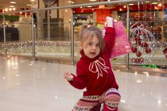 Emotional little girl in a red sweater in the shopping mall. Portrait of a pretty little girl in a red sweater with gifts at the beautifully decorated lights in Stock Photo