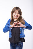 Portrait of a pretty little girl showing heart sign Royalty Free Stock Photos
