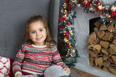 Portrait of pretty little girl sits with a book on a chair near a fireplace in Christmas at home Stock Images