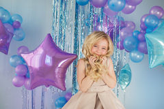 Portrait of Pretty little girl sits with a lot of color balloons and holds a hair. Portrait of Pretty little girl sits in a studio with a lot of color balloons Royalty Free Stock Images