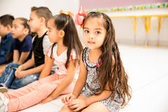 Cute little preschool girl in a classroom. Portrait of a pretty little girl sitting on the floor during class and making eye contact royalty free stock photo