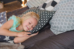 Portrait of a pretty little girl sleeps and smiles. Under a plaid in a bed Royalty Free Stock Photo
