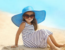 Portrait of pretty little girl in a striped dress and straw hat Royalty Free Stock Image