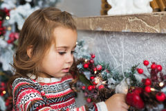 Portrait of pretty little girl touches a Christmas toy at home Royalty Free Stock Images
