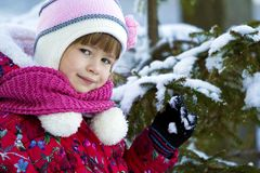 Portrait of pretty little girl in winter clothes near snow cover Royalty Free Stock Photo