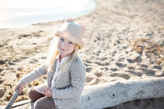 Portrait of a pretty little girl wit a light hat and knitted jacket on a beach Stock Images