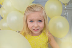 Portrait of a pretty little girl with a yellow balloons. Portrait of a beautiful little girl in a yellow dress with a yellow balloons Stock Image