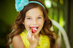 Portrait of a pretty little girl in yellow dress eats a big strawberry  with a cream Royalty Free Stock Images