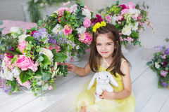Portrait of a pretty little girl in a yellow dress sits near a flowers in a studio Royalty Free Stock Images