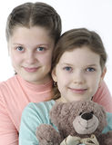 Portrait of pretty little girls holding teddy bear on white Stock Images