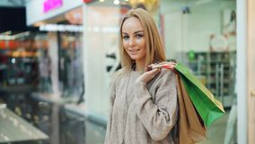 Portrait of pretty long-haired blonde in trendy clothing looking at camera and smiling standing alone in shopping mall stock video