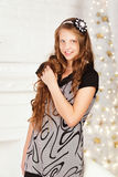 Portrait of pretty long-haired smiling teen girl in dress in int Stock Images