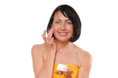Portrait of pretty mature woman using face cream Royalty Free Stock Images