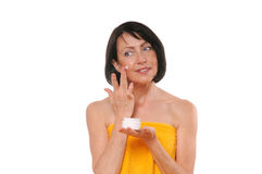 Portrait of pretty mature woman using face cream Royalty Free Stock Photo