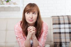 Portrait of pretty middle age woman praying and dreaming at home background. Menopause. Copy space. royalty free stock photos