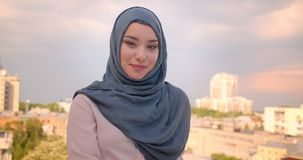 Portrait of pretty muslim female student in hijab smiling happily into camera standing at great city view. stock footage