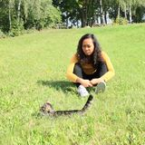 Sad girl watching a cat. Portrait of pretty Papuan girl with curly hair dressed in yellow t-shirt, black pants and white shoes - smiling young Indonesian woman Royalty Free Stock Images