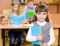 Portrait of pretty preschool girl with books in classroom.  royalty free stock photo