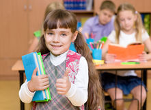 Portrait of pretty preschool girl with books in classroom showing thumb up Stock Photography
