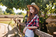 Portrait of pretty redhead cowgirl leaning on the ranch fence Royalty Free Stock Images