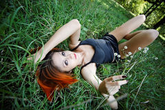 Portrait of pretty redhead girl in the grass Royalty Free Stock Image