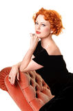 Retro portrait of vintage beauty. Portrait of pretty redhead in vintage forties dress on chaise Royalty Free Stock Images