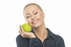 Portrait of Pretty Relaxing Blond Female Holding Green Apple in Royalty Free Stock Image