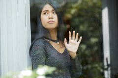 Pensive young woman looking through window royalty free stock image