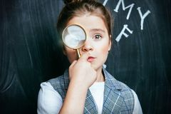 Portrait of pretty schoolgirl. A portrait of a cute girl standing with a magnifier over a blackboard. School, education stock images