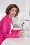 Portrait of pretty secretary sitting in pink jacket at desk. Royalty Free Stock Photography