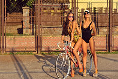 Portrait of pretty young women in swimsuits with bicycle Royalty Free Stock Images