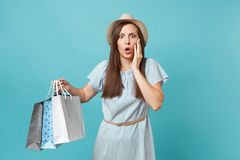 Portrait pretty shocked sad beautiful caucasian woman in summer dress, straw hat holding packages bags with purchases stock photo