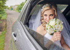 Portrait of pretty shy bride in a car window Stock Photos