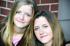 Portrait - Pretty Sisters. Portrait of two beautiful teenage sisters against a brick wall at school Stock Photo