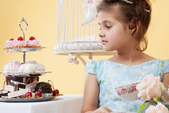Portrait of pretty smart girl looking at sweets Stock Image